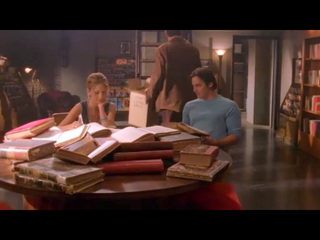 A screenshot from Buffy the Vampire Slayer, with two high schoolers at a table piled high with dusty old books.